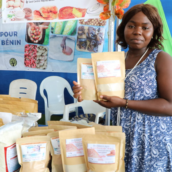 A woman stands with products at a market