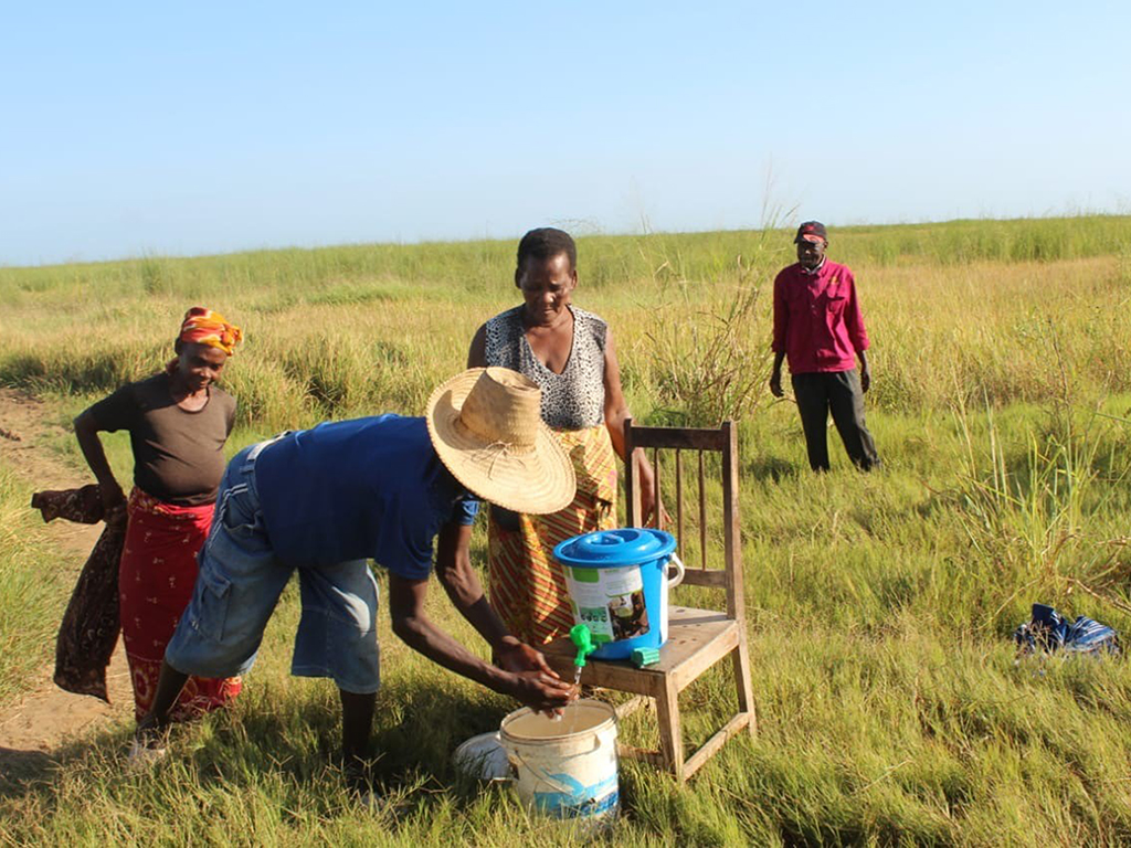 Farmers wash their hands at a field handwashing station.