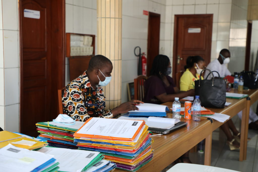 In the foreground a man wears a mask while processing documents; others practice social distancing.