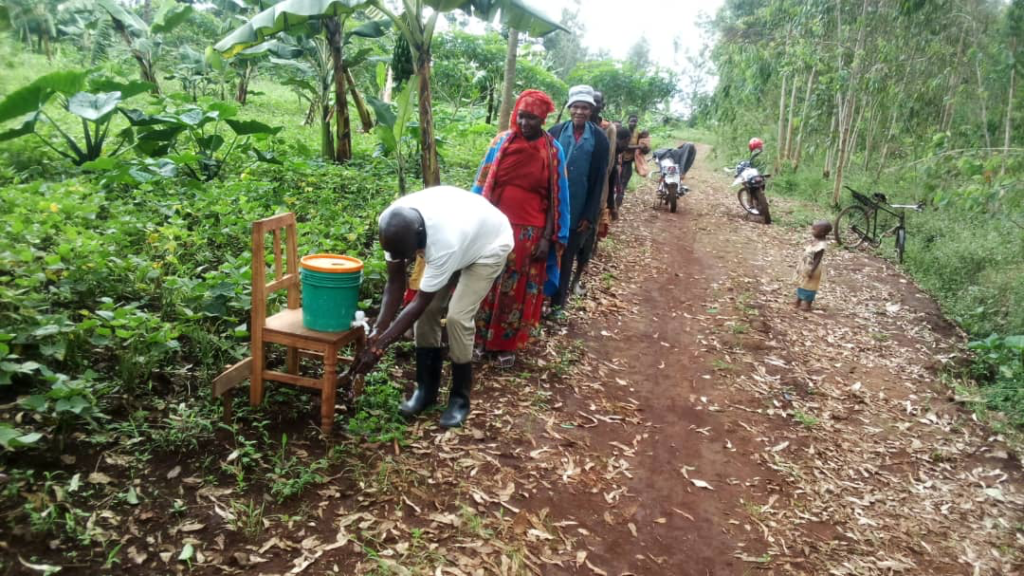 Burundian farmers line up to wash hands at a field day