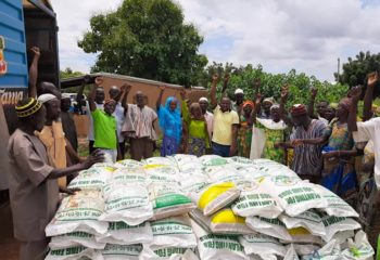 A group of farmers stands around a pallet of seed or fertilizer bags