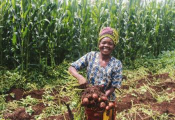 a woman displays her potato harvest